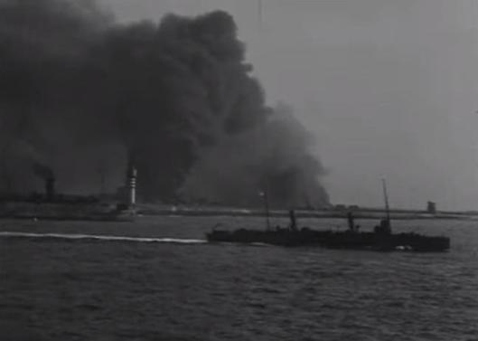 As HMS Whitehall enters Dunkirk harbour, other vessels set sail for England, with a pall of smoke in the background.