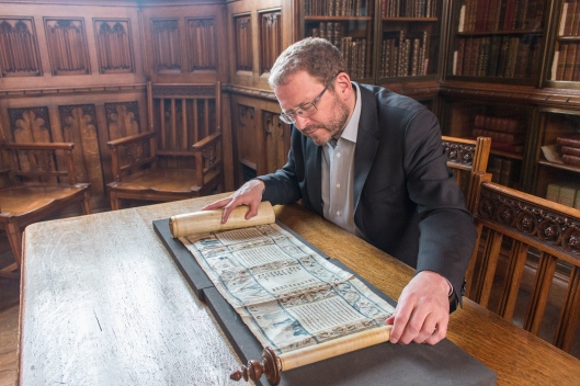 Prof. Emile Schrijver examining an Esther Scroll, Rylands Hebrew MS 22.