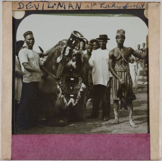 Lantern slide photograph of a group of African men, one of whom is dressed in a ceremonial outfit made from leopard skin and feathers
